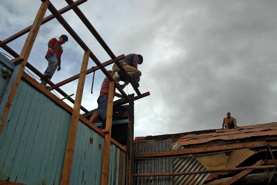 Des Cubains réparent leur maison après le passage... (Photo Afp)