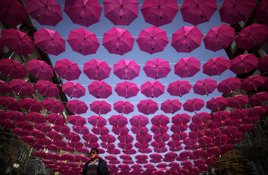 Un homme marche au centre-ville de Sofia en Bulgarie sous une installation temporaire de 400 parapluies lors d'une campagne de financement de recherche contre le cancer du sein | 26 octobre 2012