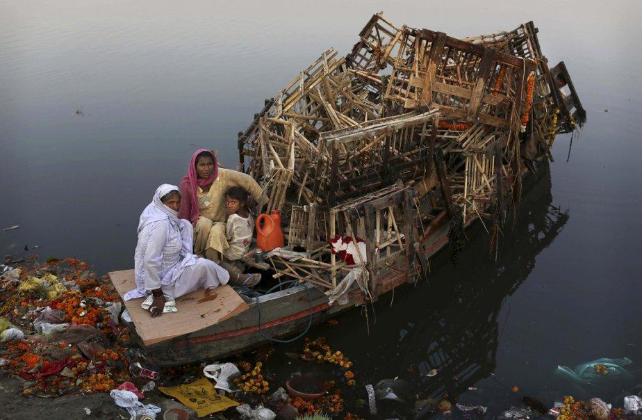 Une famille indienne récupère des structures de bois des eaux de la rivière Yamuna au lendemain du festival Durga Puja à New Delhi, en Inde. Des milliers d'effigies sont laissés par les fidèles dans le fleuve sacré dans le cadre de la fête qui commémore le meurtre d'un roi démon par la déesse Durga. | 26 octobre 2012