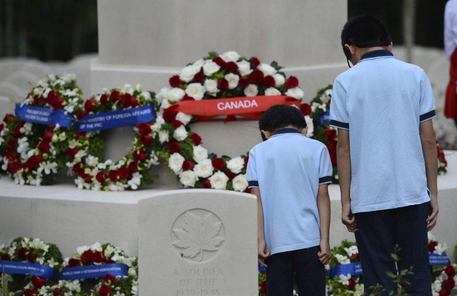 Deux petits garçons se recueillent au cimetière militaire Sai Wan de Hong Kong, en Chine, où reposent 283 soldats canadiens tués lors de la Deuxième Guerre mondiale. Le premier ministre Stephen Harper s'y est rendu, dimanche, pour le Jour du Souvenir. | 11 novembre 2012