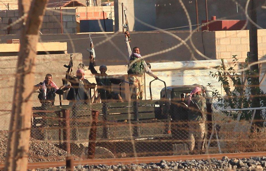 Des soldats brandissent leurs armes à Rass Al-Aïn,près... (PHOTO REUTERS)