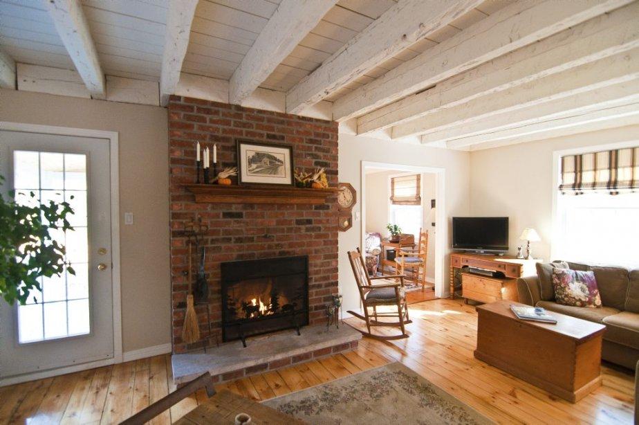 L'entrée du salon a été élargie, dévoilant dès le hall cette pièce au plafond rustique. La porte donne sur un porche d'été. | 16 novembre 2012