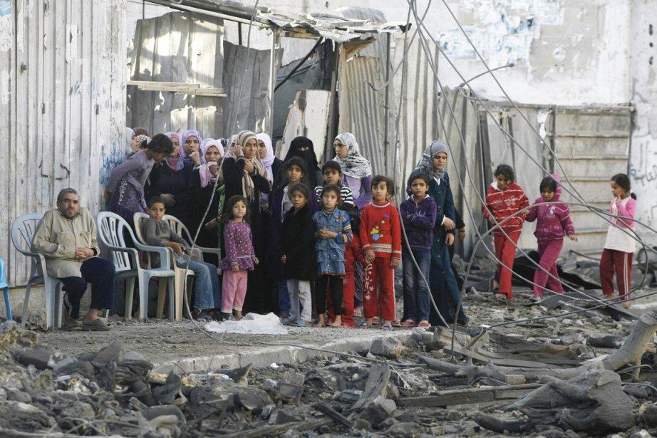 Plusieurs membres d'une famille palestinienne observent, impuissants, les ruines de leur demeure. | 19 novembre 2012