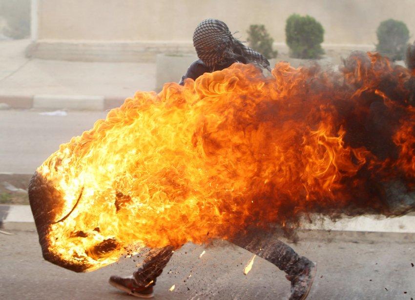 Un étudiant de l'Université de Beir Zeit, à Beitunia, en Cisjordanie, pousse un pneu en feu alors que des militants, manifestant pour dénoncer les bombardements israéliens sur Gaza, affrontent des soldats de Tsahal pour la deuxième journée consécutive. | 19 novembre 2012