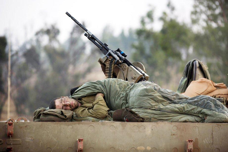 Un soldat israélien dort  couché sur son char d'assaut, alors que les troupes de Tsahal ont  pris position à la frontière de Gaza, en prévision d'un éventuel déploiement terrestre. | 19 novembre 2012