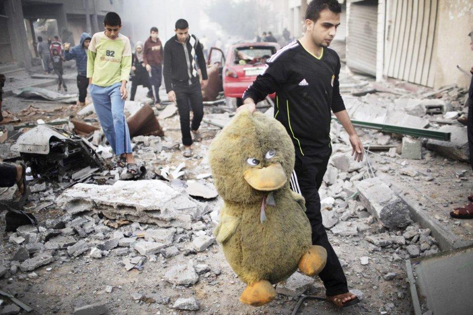 Un Palestinien récupère un canard en peluche géant des décombres de cette rue de Gaza City, bombardée par l'armée israélienne, le 19 novembre. | 19 novembre 2012