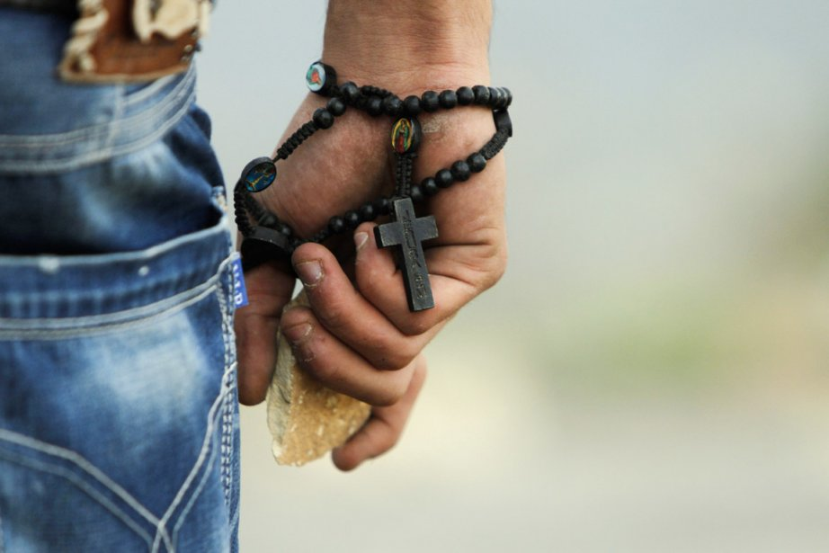Un manifestant palestinien tient une roche dans sa main alors qu'un chapelet est enroulé autour de son poignet, lors d'affrontements avec des militaires israéliens, en banlieue de Ramallah, le 19 novembre. | 19 novembre 2012
