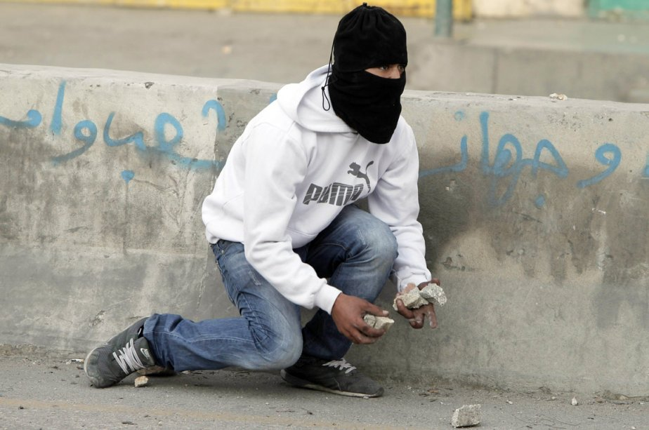 Un «lanceur de pierre» palestinien s'accroupit pour ramasser des munitions, lors de heurts avec des soldats israéliens au point de contrôle de Qalandia, en Cisjordanie. | 19 novembre 2012