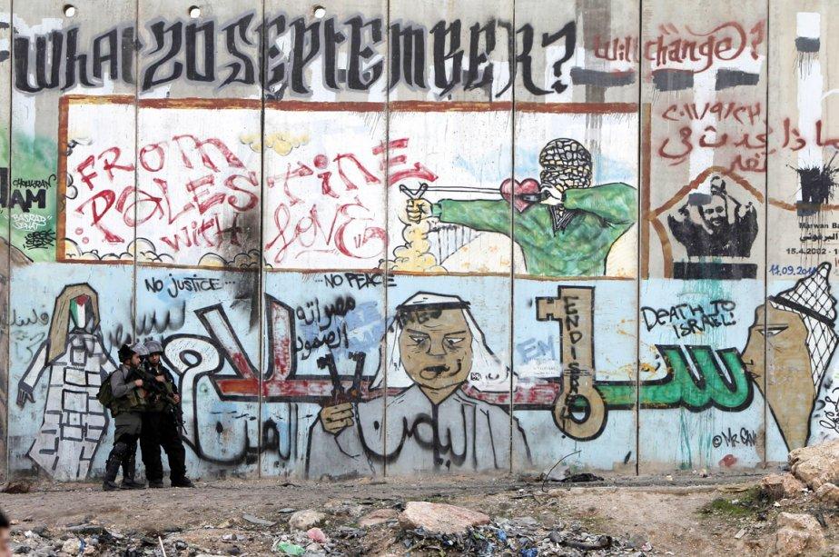 Deux soldats israéliens prennent position lors d'affrontements avec des manifestants palestiniens venus dénoncer les bombardements de Tsahal sur Gaza, à un point de contrôle de Cisjordanie, le 19 novembre. | 19 novembre 2012