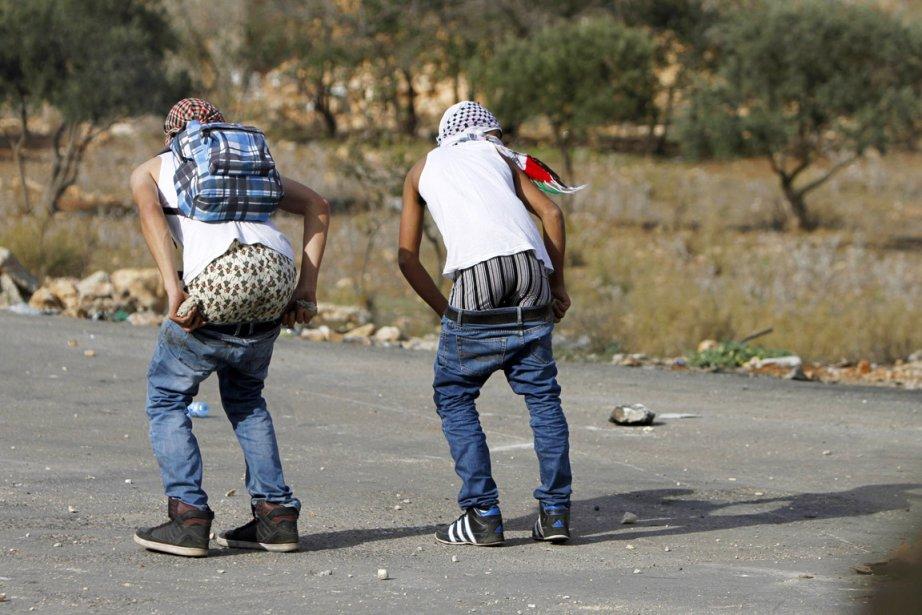 Deux «lanceurs de pierre» palestiniens narguent les forces de sécurité israéliennes, lors de heurts survenus en banlieue de Ramallah, en Cisjordanie, le 18 novembre | 19 novembre 2012