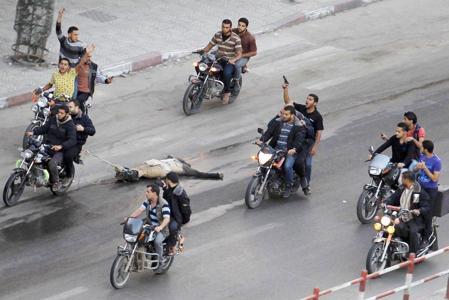 Des Palestiniens à motos tirent le cadavre d'un... (PHOTO SUHAIB SALEM, REUTERS)