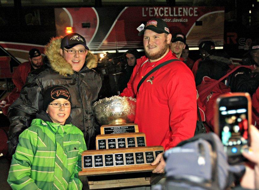 Porteur de la coupe Vanier, remportée à Toronto vendredi, Jean-Alexandre Bernier du Rouge et Or a partagé le trophée avec les fans venus accueillir l'équipe à leur arrivée à Québec, samedi. | 25 novembre 2012