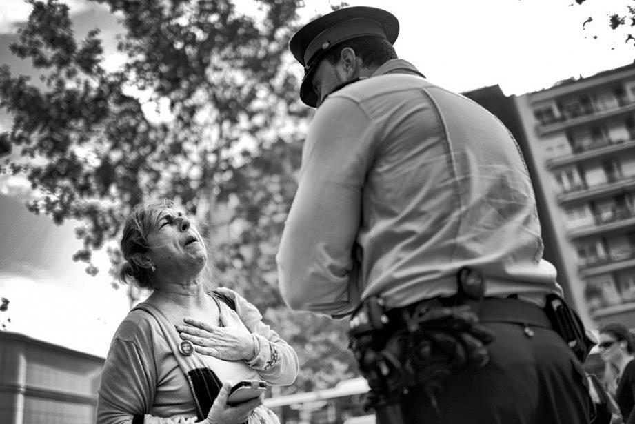 Une femme plaide sa cause devant un policier posté devant l'entrée d'une banque lors d'une manifestation à Barcelone | 5 décembre 2012