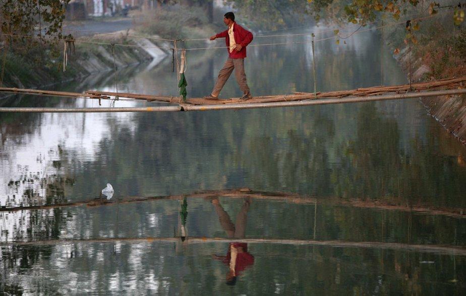 Un homme sur un pont de corde en banlieue de Jammu en Inde. | 7 décembre 2012