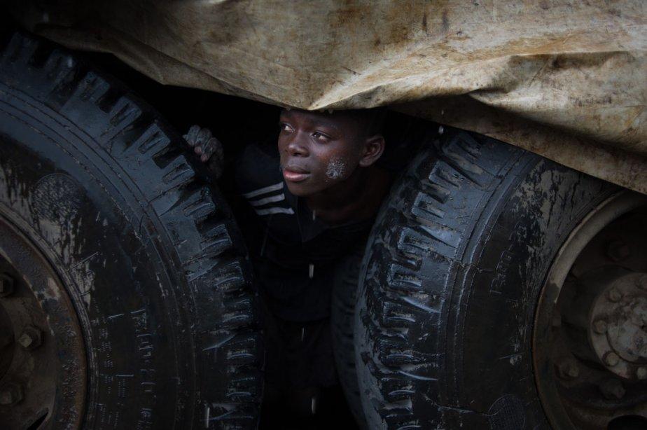 Un jeune réfugié congolais se protège de la pluie sous un camion au camp de Mugunga | 7 décembre 2012