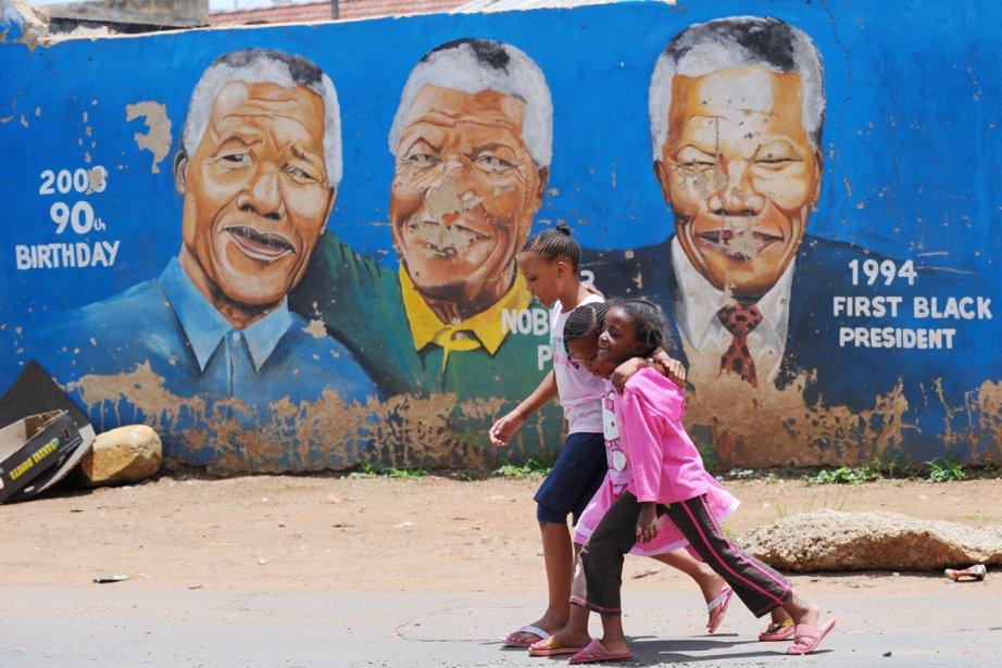 Trois jeunes filles passent devant une murale peinte... (PHOTO ALEXANDER JOE, AFP)