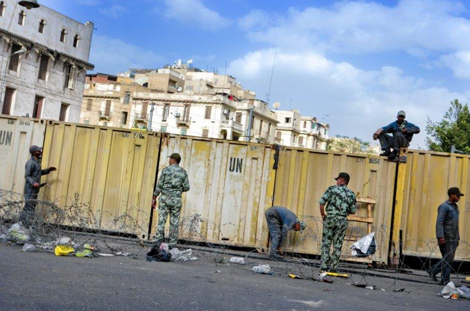 Le périmètre entourant le palais est protégé par une clôture formée de murs de béton et de conteneurs. | 10 décembre 2012