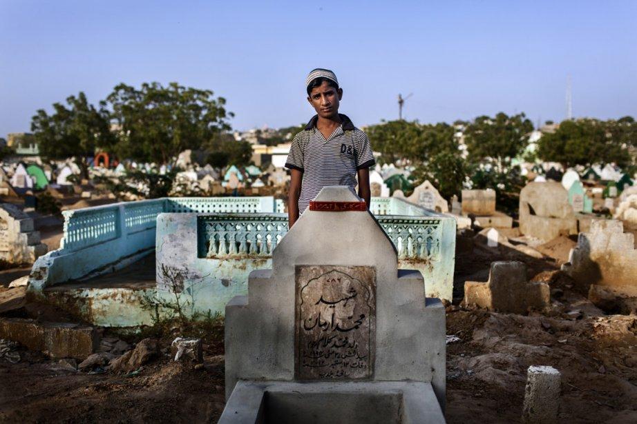 Arzahallam, 12 ans, devant la tombe de son frère Azman. | 11 décembre 2012