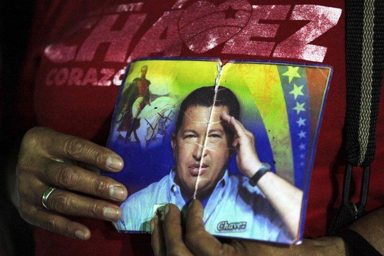 Une supporter de Hugo Chavez tient sont portrait... (Photo: AP)