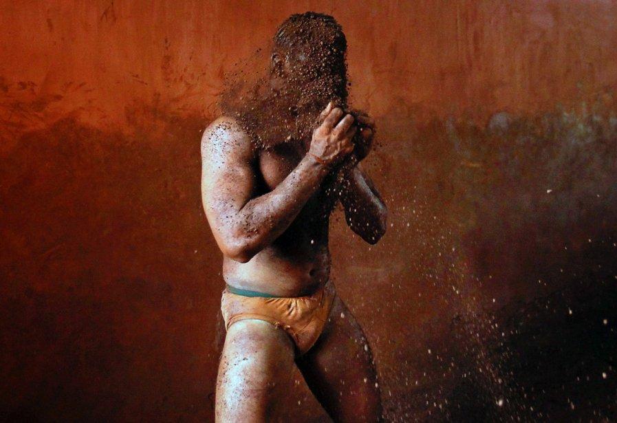 Prêt au combat - Un lutteur de Kolhapur, au sud de Mumbai, enduit son corps de terre pour en améliorer l'adhérence, avant de sauter dans une arène de kushti, la lutte traditionnelle indienne. De moins en moins d'Indiens apprennent les rudiments du kushti, préférant la lutte sur tapis qui les mènera aux compétitions internationales. | 12 décembre 2012