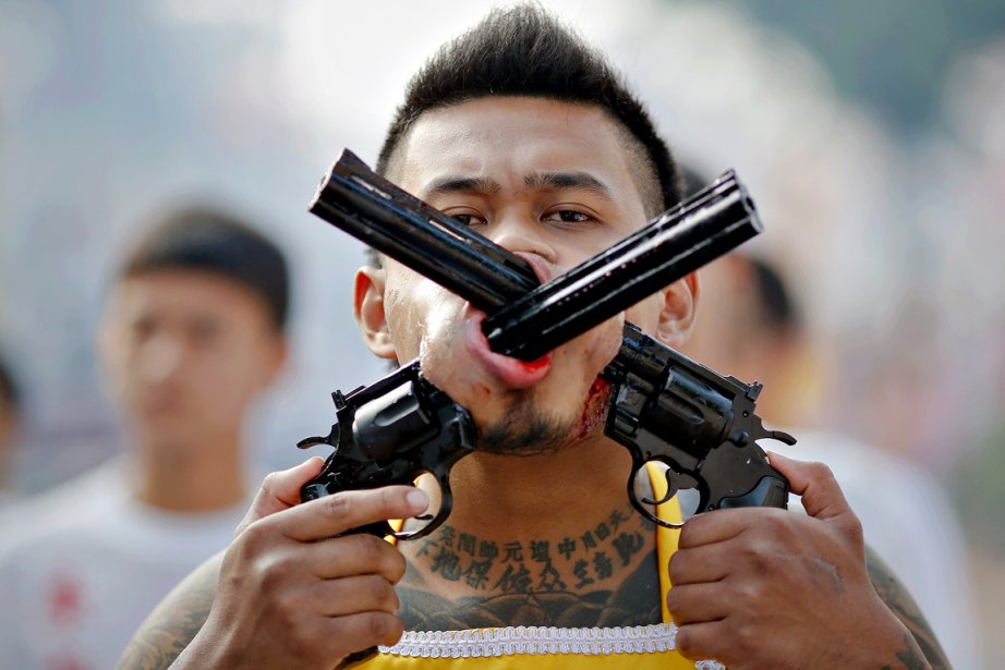 Piercing extrême - Un fidèle du temple chinois Bang Neow, à Phuket en Thaïlande, parade fièrement, deux pistolets en guise de piercing. Beaucoup de participants du Festival végétarien, qui se tient chaque automne dans la ville, voient le piercing comme une façon de se rapprocher des dieux. La croyance veut que les divinités chinoises protégeront de la souffrance les fidèles qui s'adonnent à ces actes d'automutilation durant le neuvième mois lunaire du calendrier chinois. | 12 décembre 2012