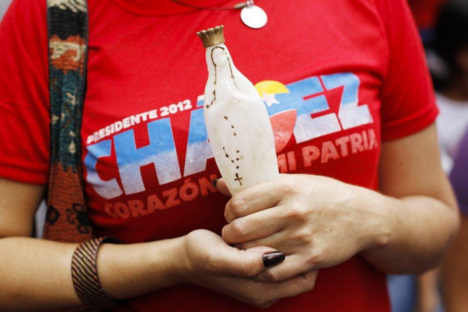 Une partisane du président Hugo Chavez, une figurine... (PHOTO CARLOS GARCIA RAWLINS, REUTERS)