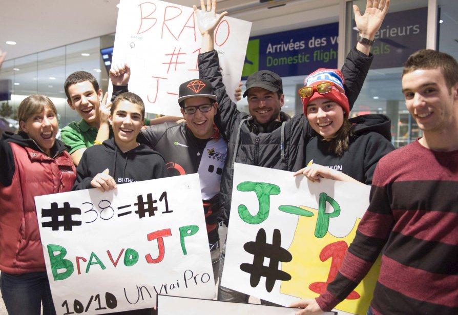 Jean-Philippe Le Guellec (les bras levés), qui a remporté sa première Coupe du monde de biathlon en carrière, a eu droit à un comité d'accueil, le 17 décembre, à l'aéroport international Jean-Lesage, pour son retour à la maison. | 18 décembre 2012