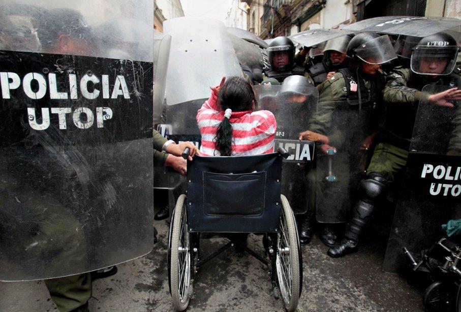 Une femme en fauteuil roulant affronte les policiers antiémeutes à... | 2012-12-18 00:00:00.000