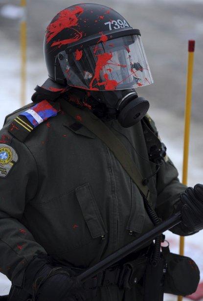 Un policier aspergé d'un liquide rouge lors d'une manifestation étudiante devant le Parlement | 20 décembre 2012