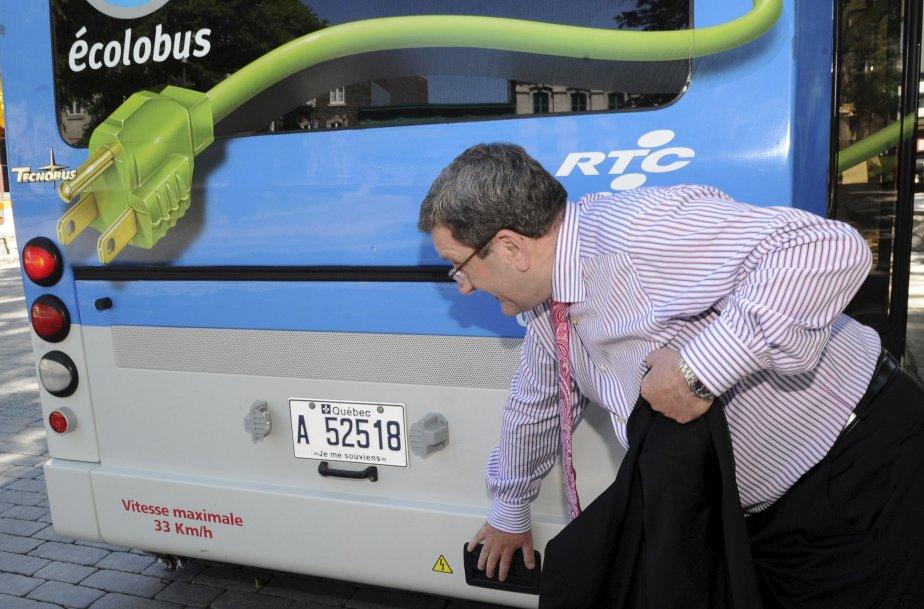 Le maire Régis Labeaume semble vérifier si les batteries de l'Écolobus ne surchauffent pas. | 20 décembre 2012