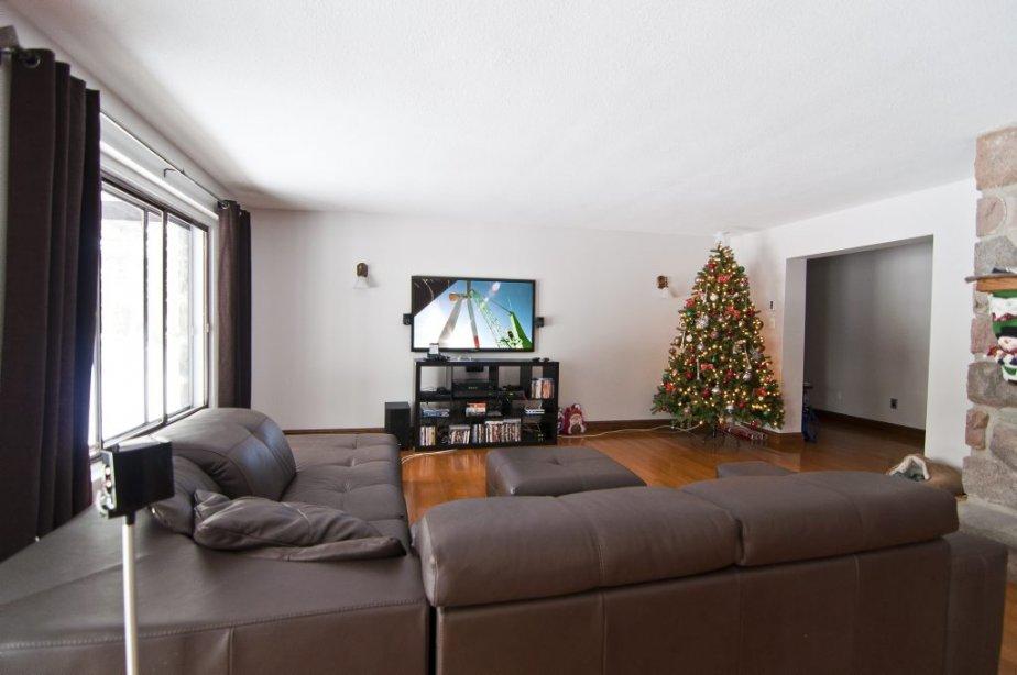 Le salon est ouvert sur la salle à manger. Un foyer traditionnel en maçonnerie orne cet espace situé à l'avant de la maison. | 21 décembre 2012