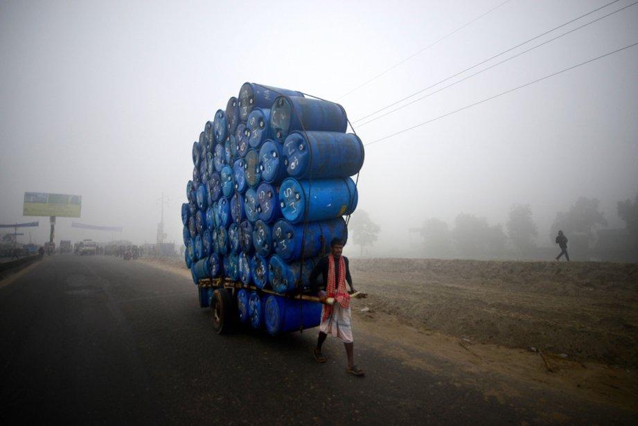 Un travailleur et ses tonneaux sur une route de Dhaka au Bangladesh. | 21 décembre 2012