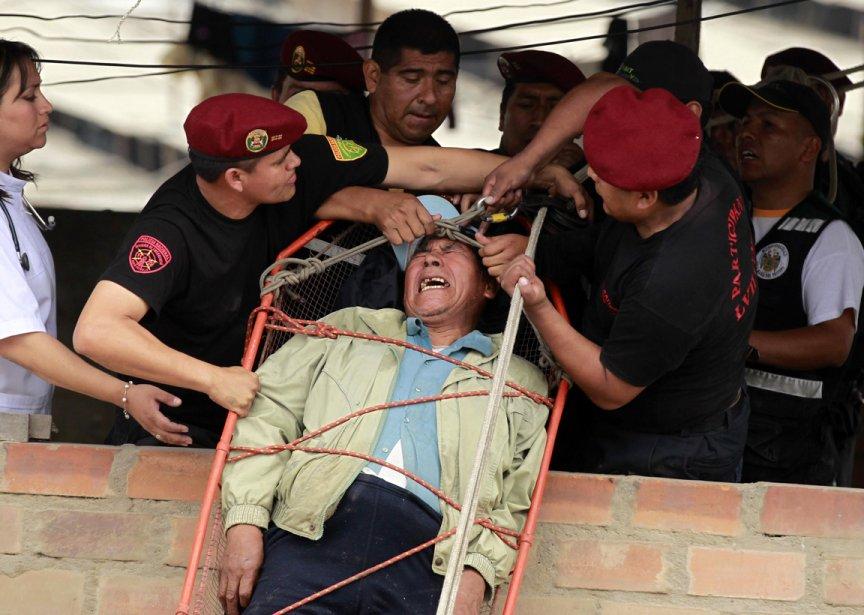 Des premiers répondants soulèvent un homme lors d'une inondation causée par un bris de conduite à Lima au Pérou | 21 décembre 2012