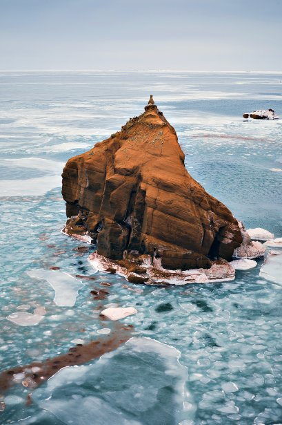Un rocher de couleur rouille, typique de la géologie particulière des Îles-de-la-Madeleine, est entouré par les glaces. Le grès ferrugineux — une pierre riche en particules de fer, très courante dans ce secteur du golfe du Saint-Laurent — tire sa couleur étonnante de l'oxydation du fer qu'il contient | 21 décembre 2012