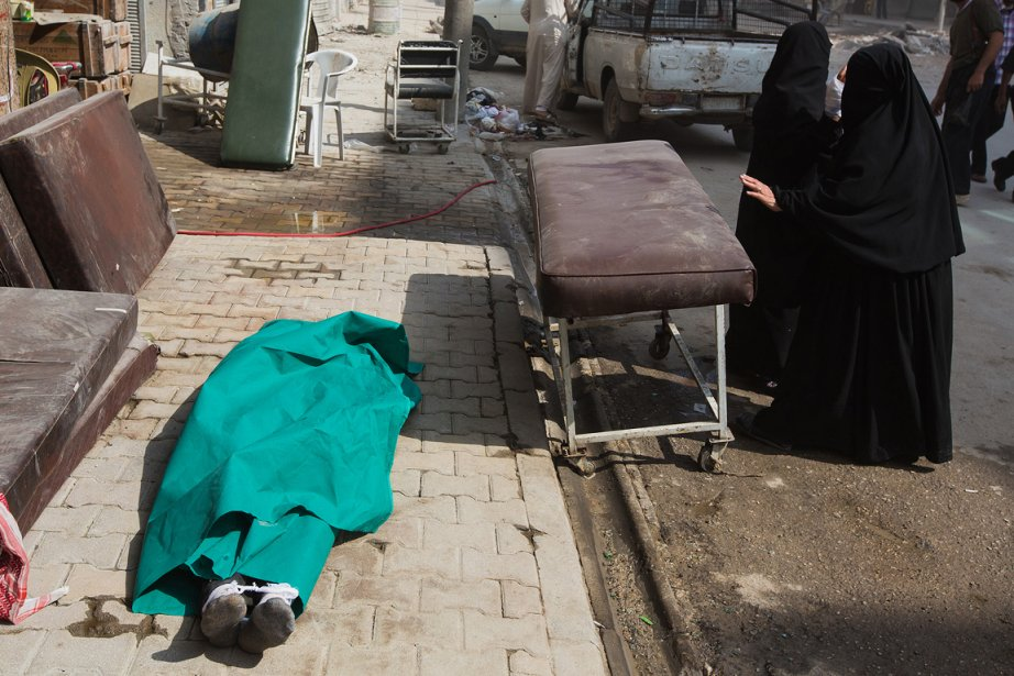Le corps d'une victime anonyme des combats, qui déchiraient Alep en septembre, repose sur le trottoir, en face de l'hôpital Dar Al Saïfa. «Le personnel n'avait pas toujours le temps de s'occuper des cadavres. Celui-là avait été déposé là en attendant, sur le chemin des femmes qui passaient dans la rue.» | 21 décembre 2012