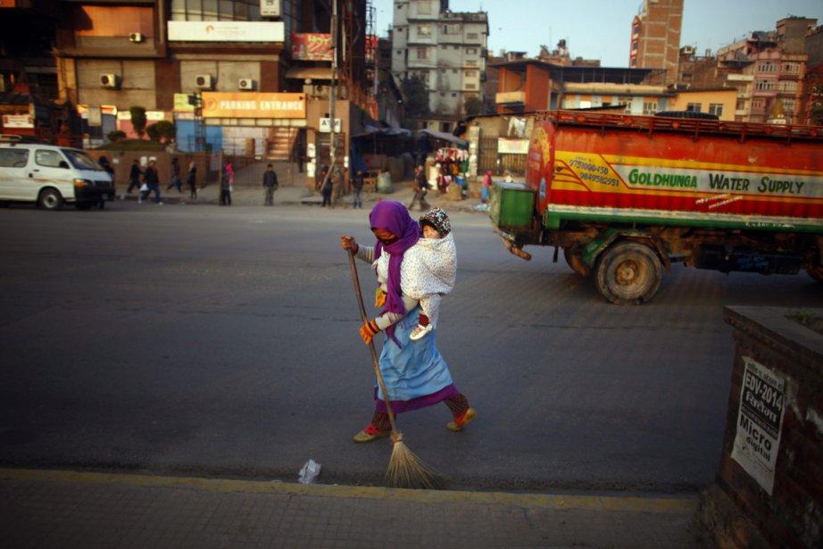 Une femme balaie une rue de Katmandou avec un bambin sur le dos | 26 décembre 2012