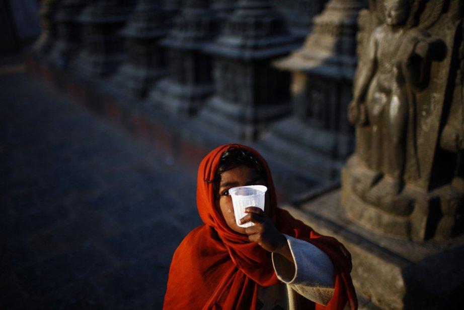 Une jeune enfant sans domicile fixe boit du thé au stupa de Swayambhunath, aussi connu comme le temple de singes. | 26 décembre 2012