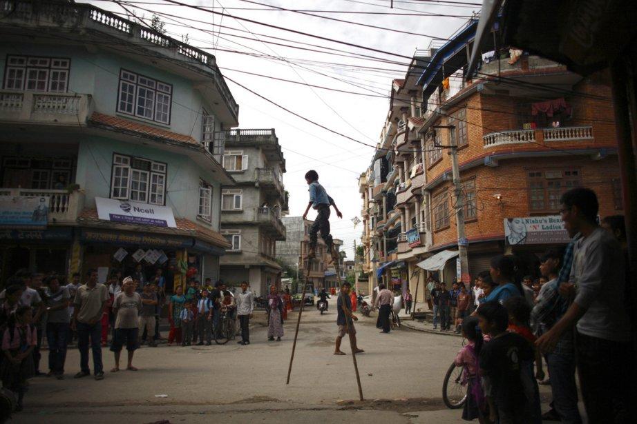 Un enfant sur des échasses amuse les passants dans une rue commerciale de Katmandou. | 26 décembre 2012