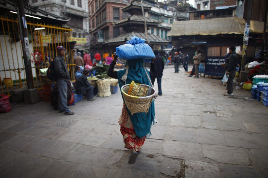 A Nepalese street vendor carries her belongings as she walks near the Ason market market in Katmandu, Nepal, Wednesday, Dec. 26, 2012. Ason is one the busiest and oldest market which is dominated by the Newar community people. (AP Photo/Nirajnan Shrestha)  Uneemployée du Marché Ason à Katmandou transporte sa marchandise. | 26 décembre 2012