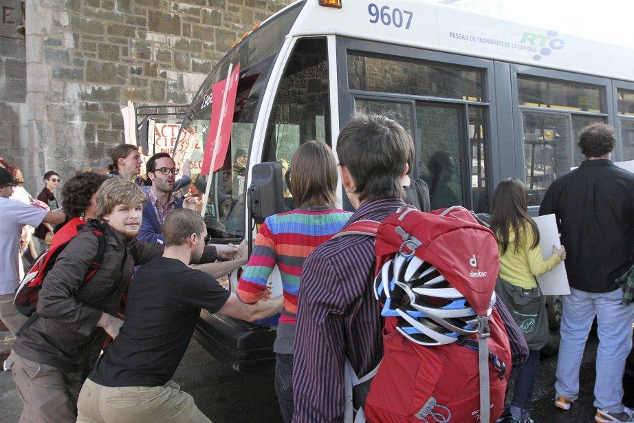 Des manifestants portant le carré rouge tentent en vain d'empêcher un autobus de circuler à la place D'Youville. | 27 décembre 2012