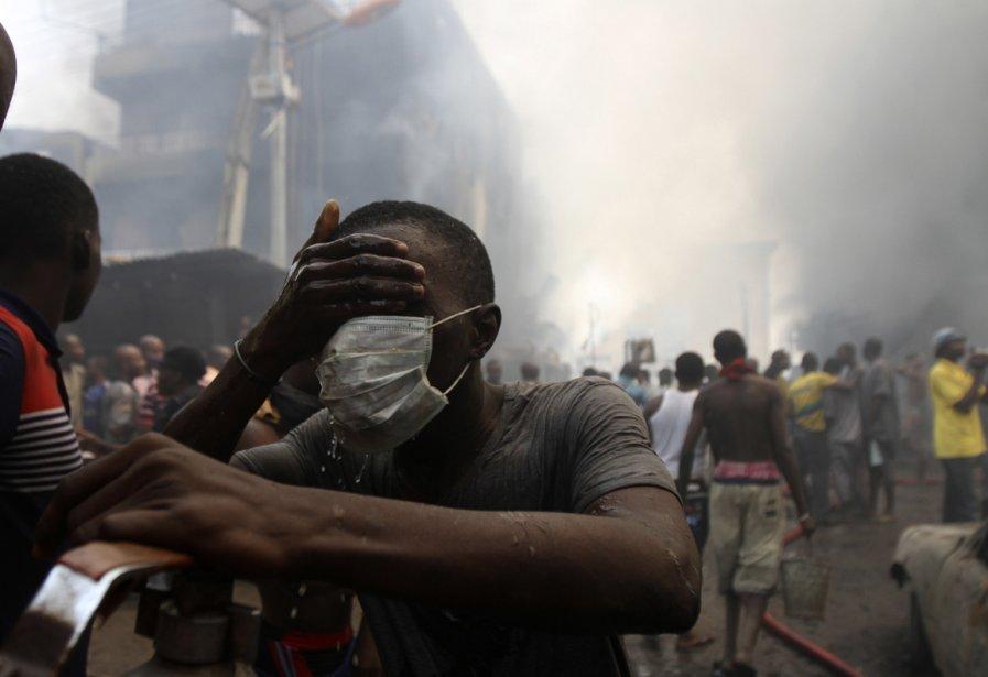 Une victime se couvre le visage, à la suite d'une explosion dans un entrepôt de feux d'artifice à Lagos au Nigeria. | 28 décembre 2012