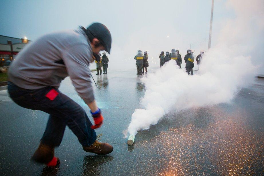 Un manifestant se penche pour ramasser une bombe lacrymogène, avant de la lancer vers les policiers. «Cette fois-là, le vent soufflait du bon côté, dit Édouard Plante-Fréchette.Mais je n'ai jamais reçu autant de gaz que ce jour-là. J'étais mal équipé. Des manifestants m'ont aidé pour que je puisse continuer à faire mon travail.» | 28 décembre 2012