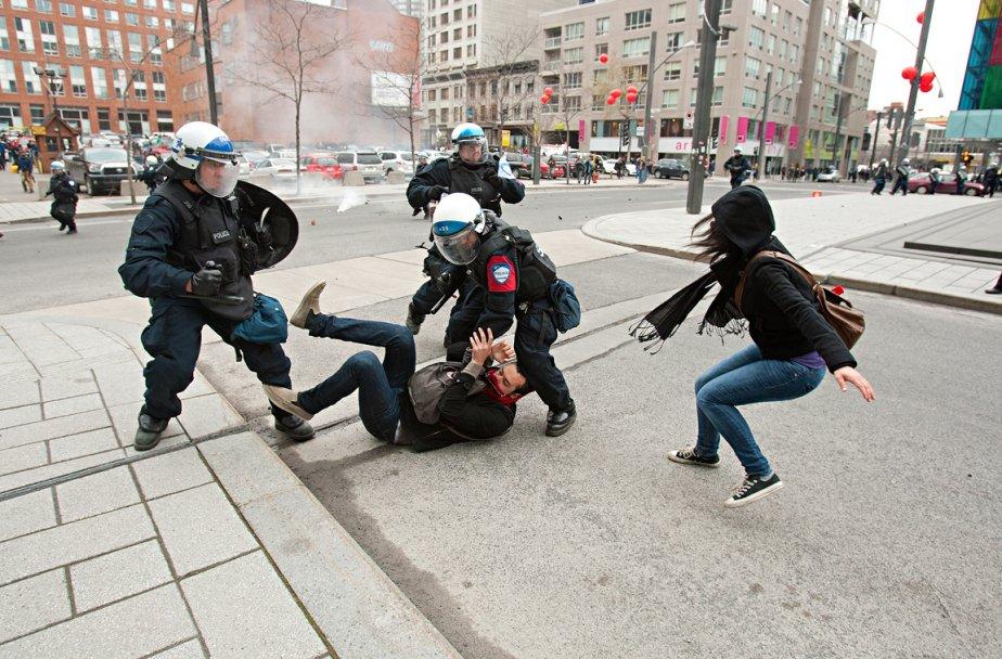 Des policiers jettent un homme au sol pendant que son amie tente de lui porter secours, lors de la manifestation du 20 avril près du Palais des congrès de Montréal, où le premier ministre Jean Charest parlait du Plan Nord.  «L'un de nos photographes, qui couvrait la manifestation, avait besoin d'une carte mémoire de toute urgence. Pendant que je courais à sa rencontre, il y a eu cette intervention juste devant moi.» | 28 décembre 2012