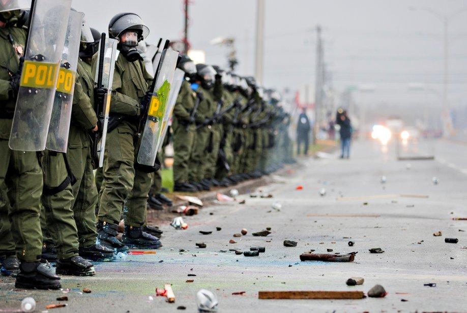 Accalmie et débris — Les policiers de la Sûreté du Québec se mettent en rang pour faire face aux manifestants. «Il y a eu une accalmie et j'ai pu m'approcher des policiers, dit Édouard Plante-Fréchette.Le sol était jonché de débris. On distingue au moins deux boules de billard à terre.» | 28 décembre 2012