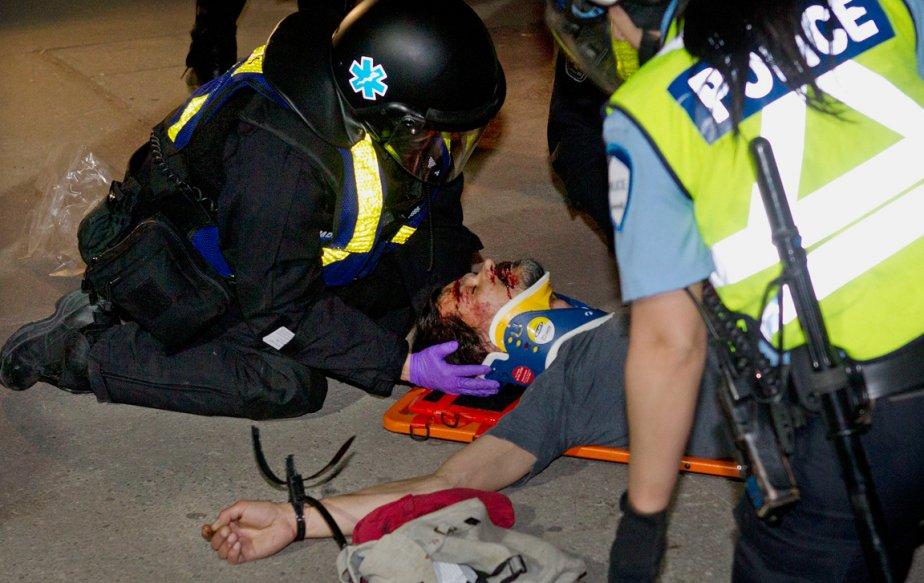 Inanimé sur un brancard d'Urgences-santé, la bouche et l'arcade sourcilière ensanglantées, un manifestant est soigné par des ambulanciers le soir du 20 mai. | 28 décembre 2012