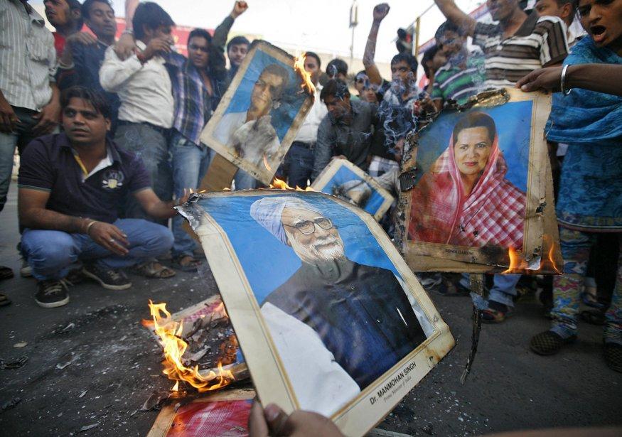 Des manifestants brûlent des portraits des politiciens au pouvoir, déçus de leur réaction à la suite du viol de l'étudiante. | 30 décembre 2012