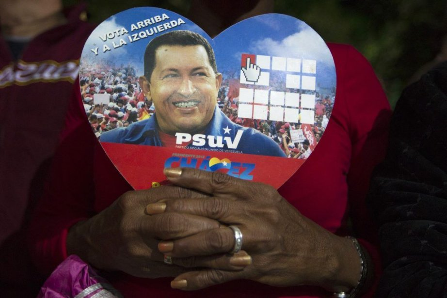 Une partisane du président Chavez tient une photo... (PHOTO Carlos Garcia Rawlins, REUTERS)