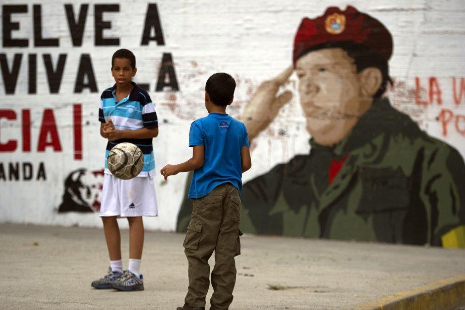 Des enfants jouent au soccer devant une fresque... (Photo Juan Barreto, AFP)