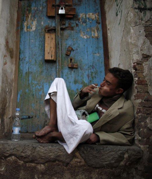 Un homme fume une cigarette et mâche du qat, un léger stimulant, dans un coin du marché de la vieille ville de Sanaa. Le qat est populaire au Yémen, où la plupart des hommes passent la moitié de la journée à en mâcher. | 7 janvier 2013