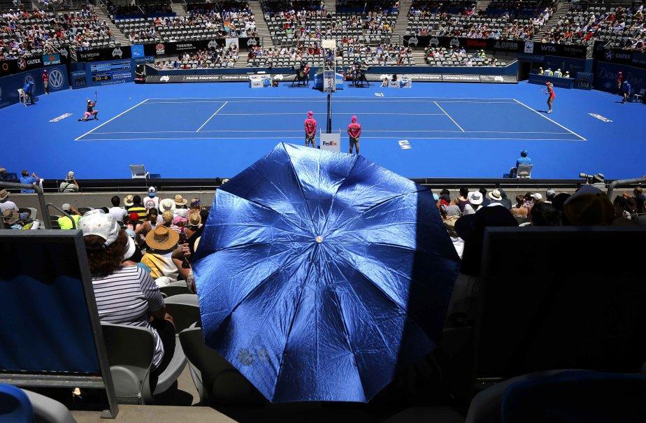 Un spectateur tient un parapluie pendant un match entre la Danoise Caroline Wozniacki (gauche) et la Polonaise Urszula Radwanska, au tournoi Sydney International. | 7 janvier 2013